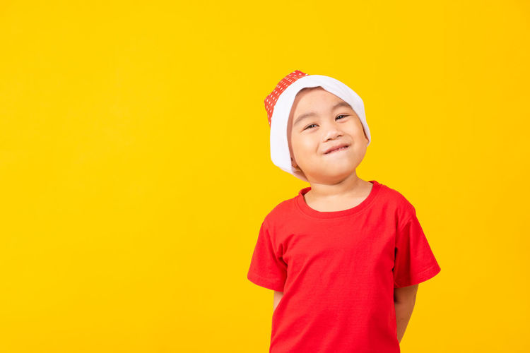 Boy looking away against yellow background
