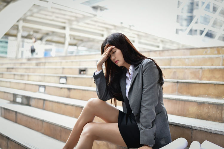 Stressed businesswoman with head in hand sitting on steps