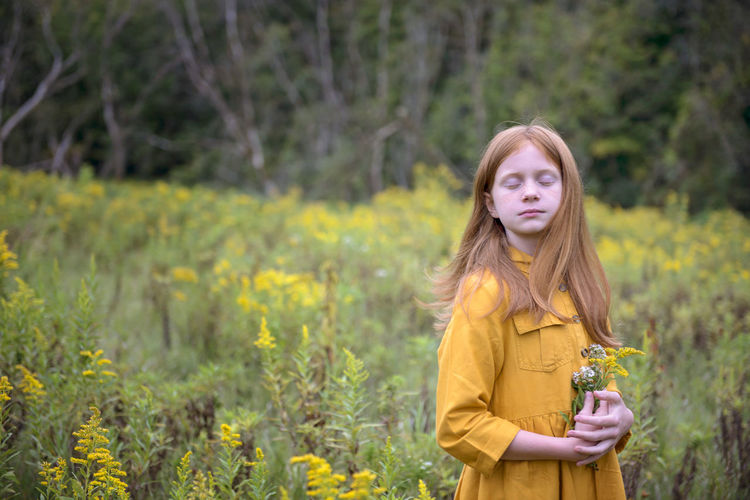 Portrait of beautiful young woman standing on yellow flowering plants