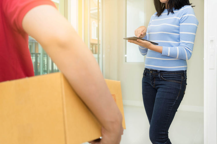 Midsection Of Man Holding Parcel With Woman Using Digital Tablet In Background