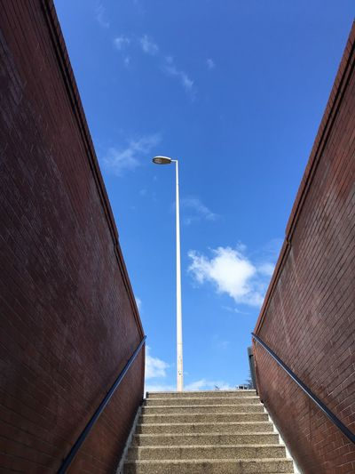 Low angle view of stairs going up and street light against sky