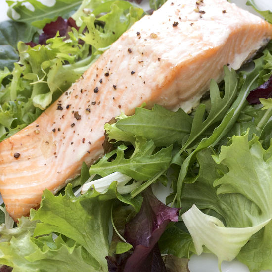 Baked Salmon steak on a bed of leaves Baked Black Pepper Close-up Fish Food Food And Drink Freshness Green Color Healthy Eating High Angle View Leaf Leaf Salad Leaves Organic Ready-to-eat Salad Salmon Seasoned Steak Still Life Selective Focus