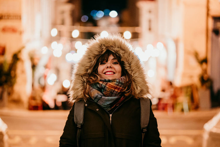 Portrait of smiling young woman in winter at night