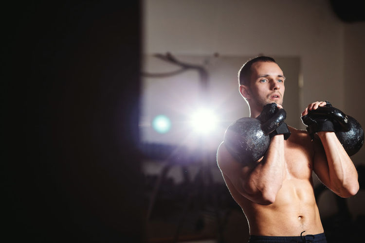 Shirtless Muscular Man Lifting Weights While Standing In Gym