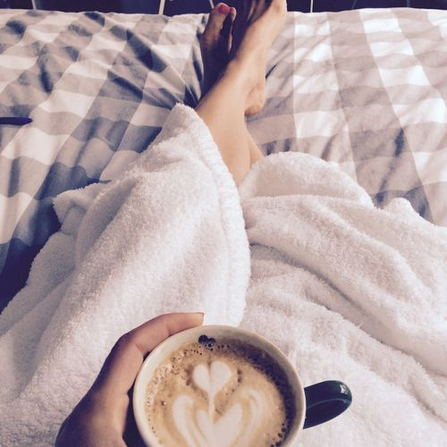 Low section of woman with coffee cup on bed
