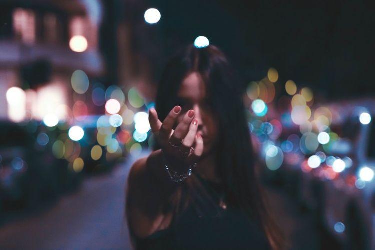 Close-up of woman hand with illuminated lights at night