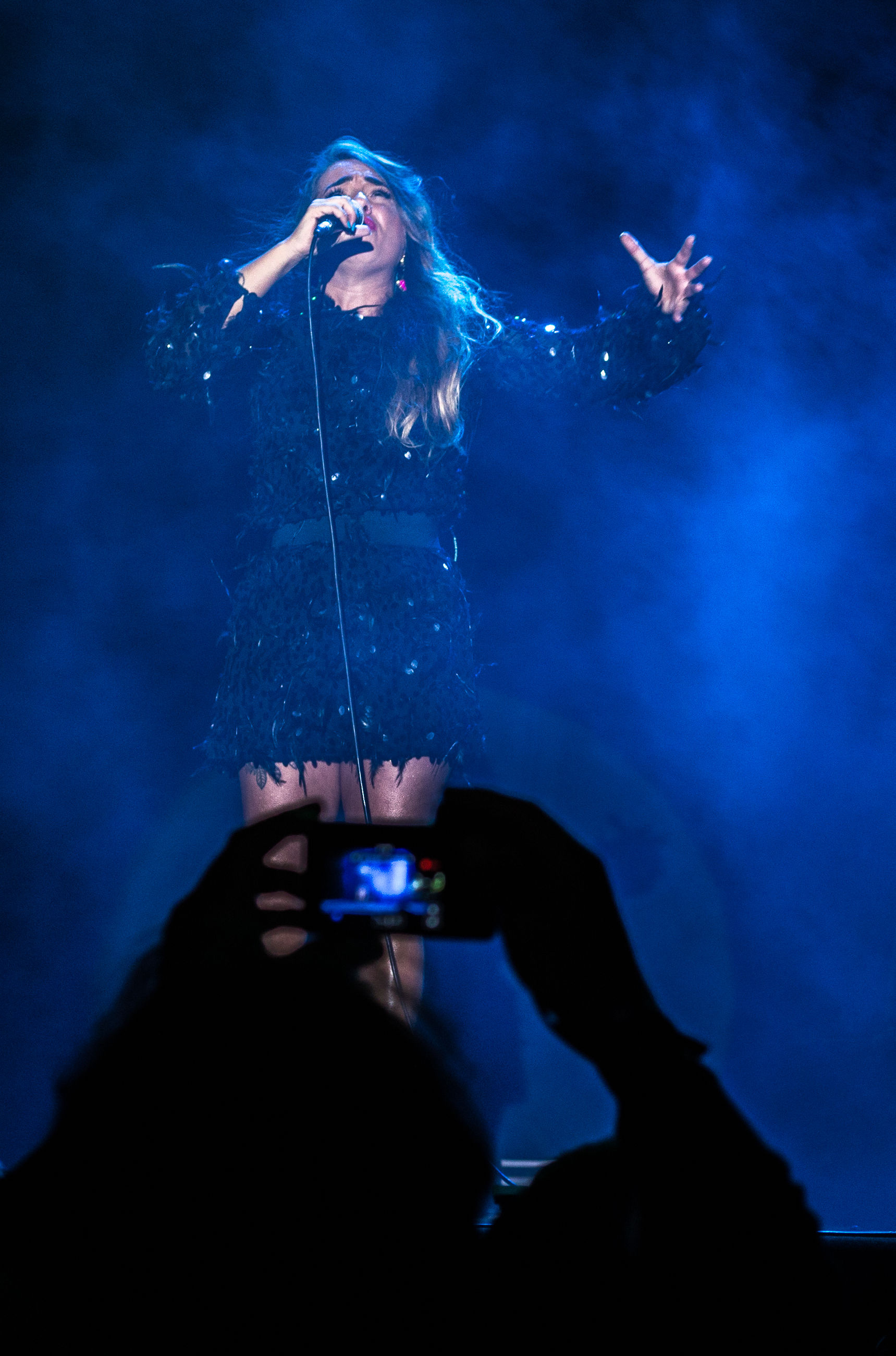 real people, night, holding, one person, water, lifestyles, leisure activity, illuminated, singing, music, arts culture and entertainment, singer, young adult, human hand, nightlife, microphone, young women, performance, outdoors, musician, people