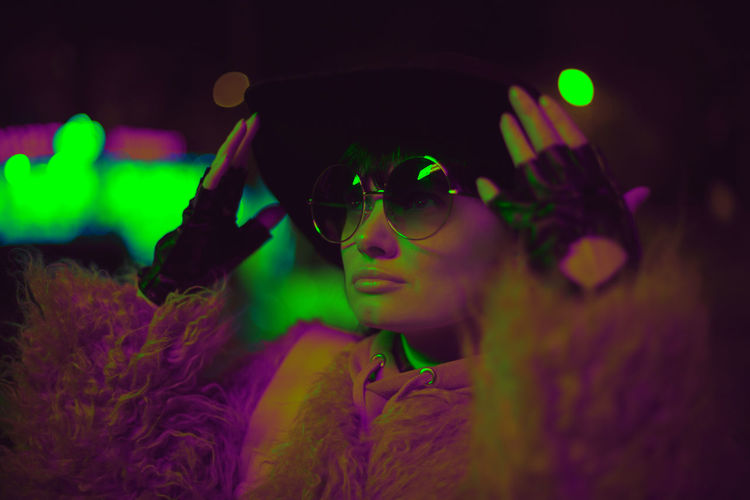 Close-up of woman wearing sunglasses and hat at night