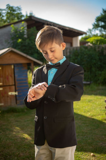 Boy Wearing Suit While Standing In Yard