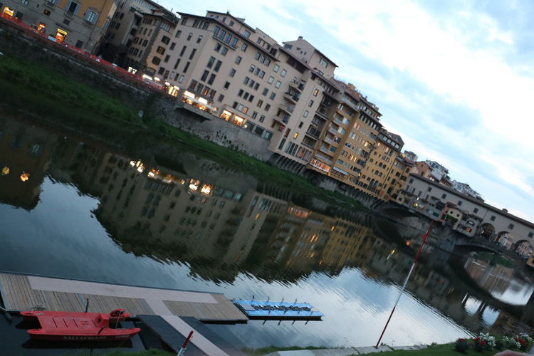 Still water, lined with colourful flowers, casting the perfect reflection of the buildings on a summer evening in Florence, Italy Grass Green Light Pink Reflection Stil Architecture Blue Bridge Buildings Clean Clear Clouds Dock Dull Dusk Evening Flowers Lining Nature Sky Still Water White Windows