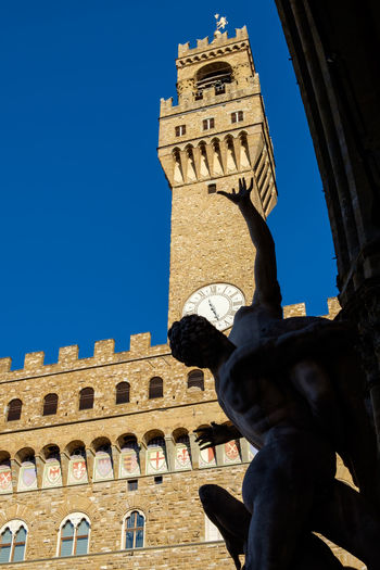 The Palazzo Vecchio is the town hall of Florence, Italy. It overlooks the Piazza della Signoria with its copy of Michelangelo's David statue as well as the gallery of statues in the adjacent Loggia dei Lanzi. Arch Architecture Blue Building Exterior Built Structure Clear Sky Famous Place Florence Florence Italy Italy Low Angle View Old Town Palazzo Vecchio PalazzoVecchio Palazzovecchiotower Sculpture Statue The Past Tourism Tower Travel Destinations