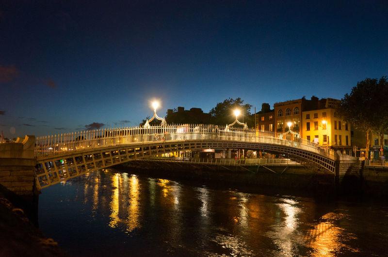 Illuminated Ha Penny Bridge Over Liffey River At Dusk