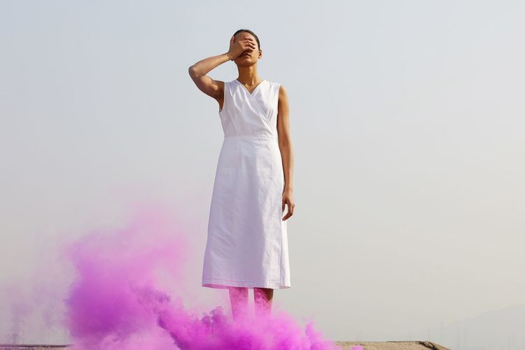 Young woman covering eyes while standing by pink distress flare against clear sky