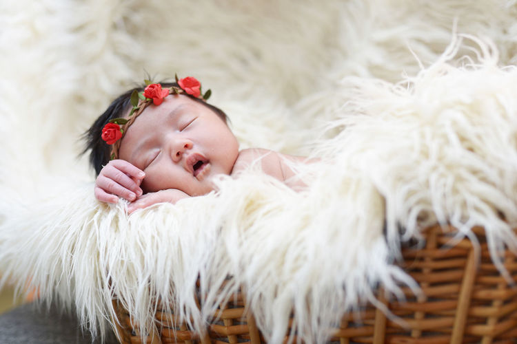 Close-up of cute baby girl sleeping on rug at home