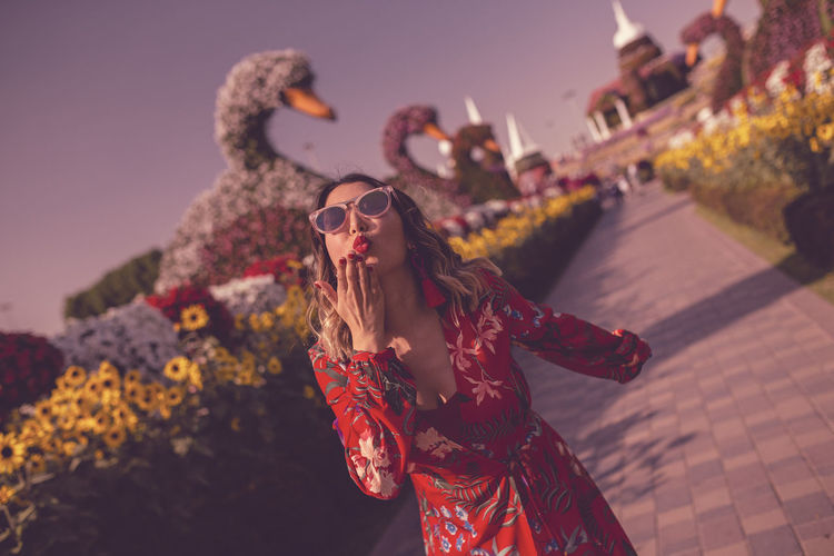 Young Woman Blowing Kiss While Standing In Ornamental Garden At Dusk