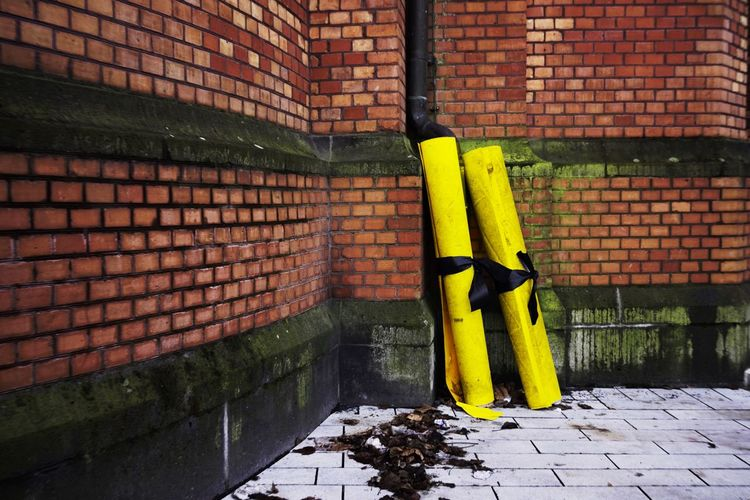 Yellow rolled tarpaulins against brick wall