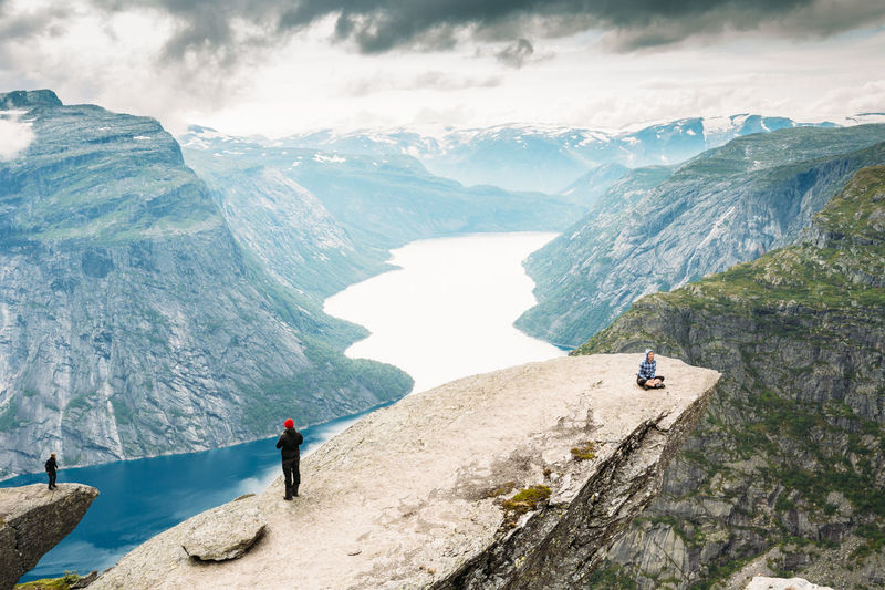 Odda, Norway - August 04, 2014: Young People Are Photographed Standing On A Rock Trolltunga - Troll Tongue In Norway. View From Rock Trolltunga - Troll Tongue. Famous High Norway Scandinavia Travel Troll Tongue Young Adventure Beutiful  Day Europe Fjord Go Higher Jorney Landscape Men Mountain Nature People Rock Sky Summer Tourism Trip Troll The Great Outdoors - 2018 EyeEm Awards