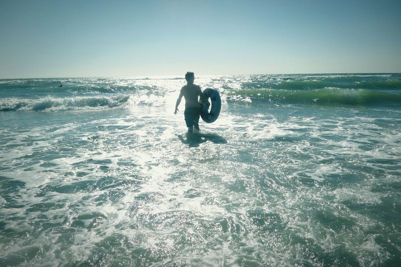 Rear View Of Man With Inflatable Ring Walking In Sea Against Sky