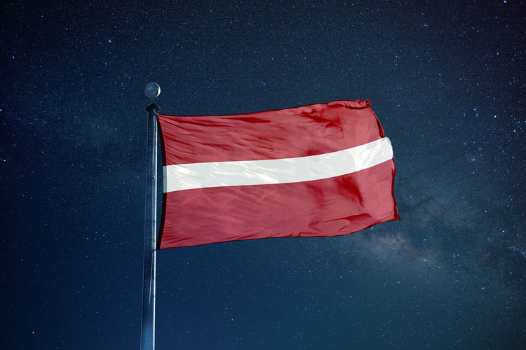 Flag of latvia against star field sky