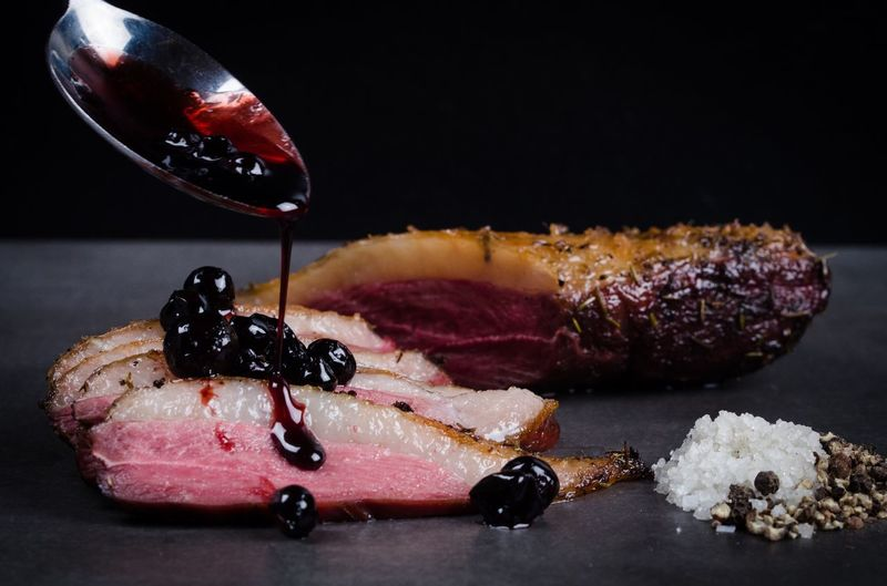 Sauce pouring on smoked meat using spoon against black background