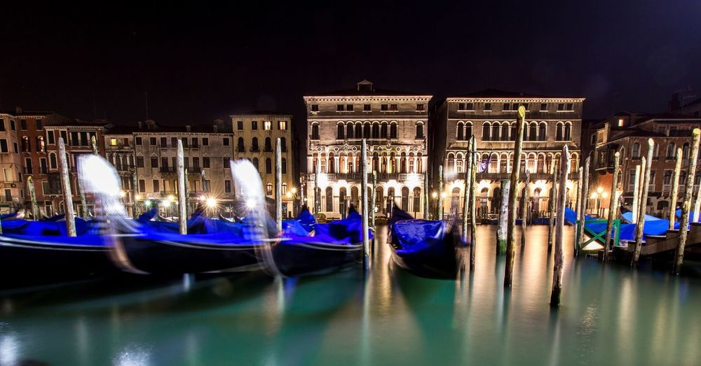Gondolas moored in grand canal against illuminated buildings during night