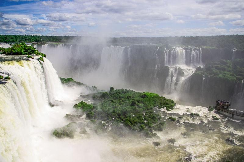 Scenic view of iguazu falls against cloudy sky