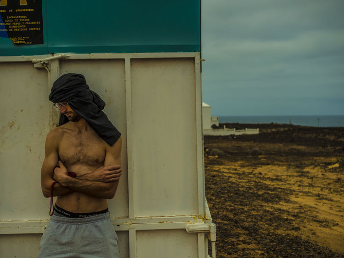 Shirtless young man with arms crossed standing against wall