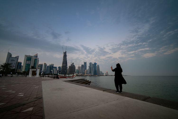 Women Capturing City Skyline in Phone Architecture Building Exterior Sky Built Structure City One Person Building Real People Water Lifestyles Skyscraper Full Length Cloud - Sky Nature Women Travel Destinations Standing Leisure Activity Tall - High Cityscape Outdoors Financial District  Ijas Muhammed Photography Qatar Doha