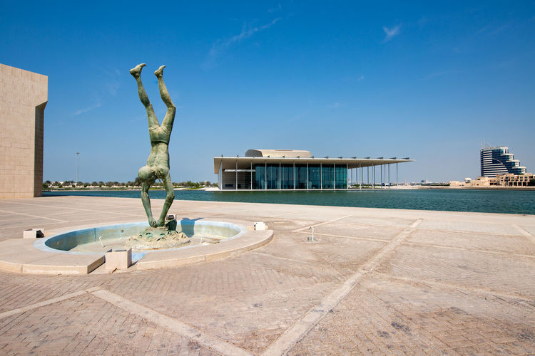 Beautiful view of the Pearl Diver monument in the Bahrain National Museum along with the Bahrain National Theater in the background Architecture Bahrain City Break Cityscape Clear Sky Day Modern Monument, National Museum National Theatre No People Outdoors Pearl Diver Pearl, Popular Sculpture Sea Sky Statue Sunlight Tourism Travel Travel Destinations Vacations Water
