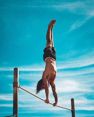 Full length of shirtless man balancing on rope against blue sky