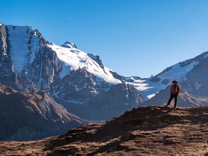 Full length of man standing on rock against mountains and sky