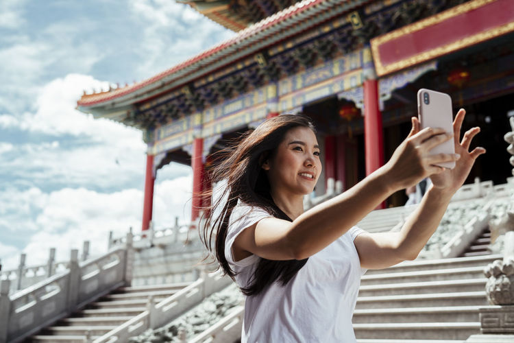 Smiling women vlogging while standing against temple