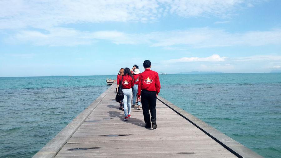 เดินชมความงามของทะเล Full Length Rear View Horizon Over Water Togetherness Sea Sky Water Day Person Tranquility Casual Clothing The Way Forward Tranquil Scene Cloud Cloud - Sky Scenics Red Blue Solitude
