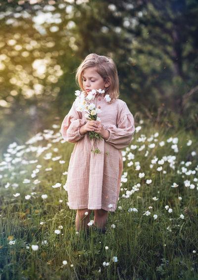Girl holding flower standing on field
