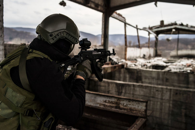 Army soldier aiming rifle while standing in building