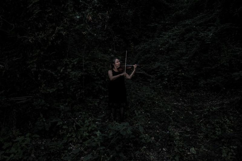 Full length of woman playing violin against plants