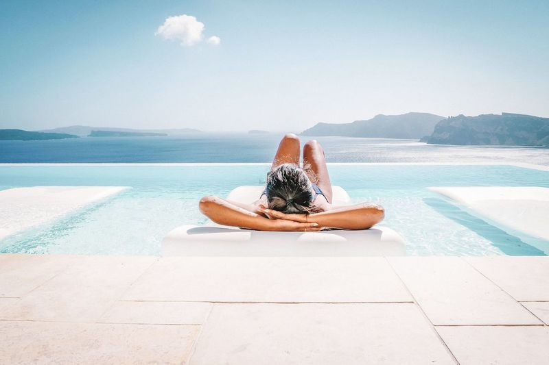 Woman relaxing on pool raft floating on swimming pool against sky