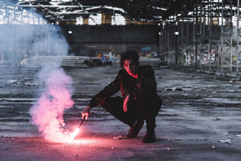 Full length of man crouching with distress flare in abandoned factory