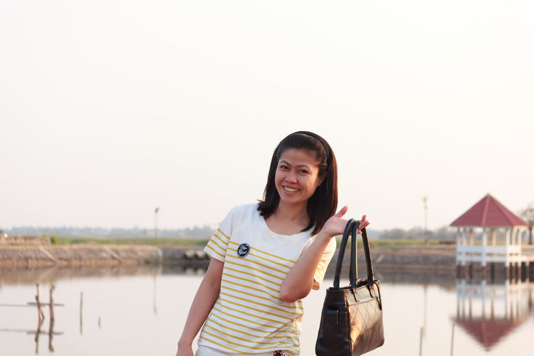 Looking At Camera One Person Portrait Standing Young Adult Front View Smiling Real People Casual Clothing Lifestyles Leisure Activity Copy Space Young Women Sky Emotion Water Three Quarter Length Focus On Foreground Beautiful Woman Hairstyle