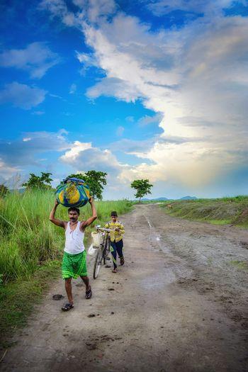 People on dirt road against sky