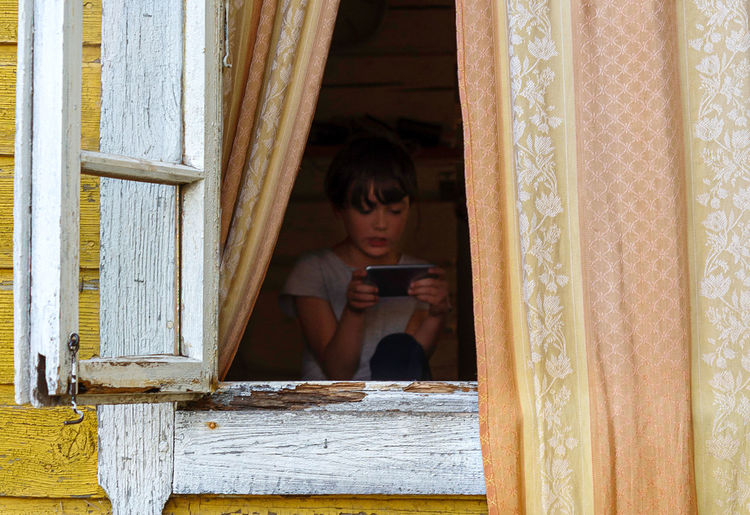 Young woman using mobile phone while sitting in mirror
