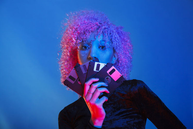 Portrait of young woman holding floppy disk against blue background
