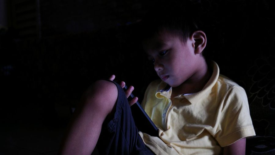 Boy using mobile phone against black background