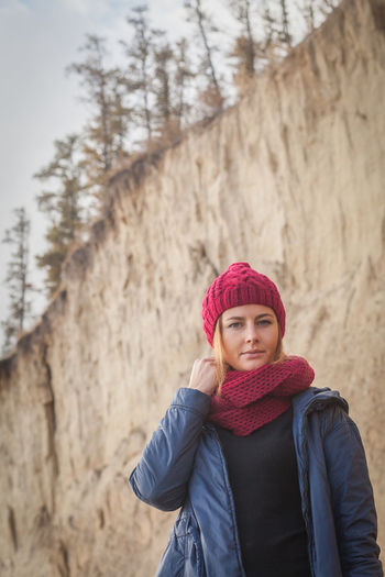 A young dark-haired woman in a knitted red hat and scarf from natural wool, a blue jacket posing