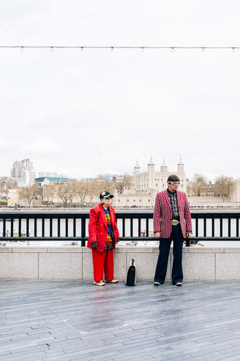 Senior Man And Woman Standing On Boardwalk Against Sky