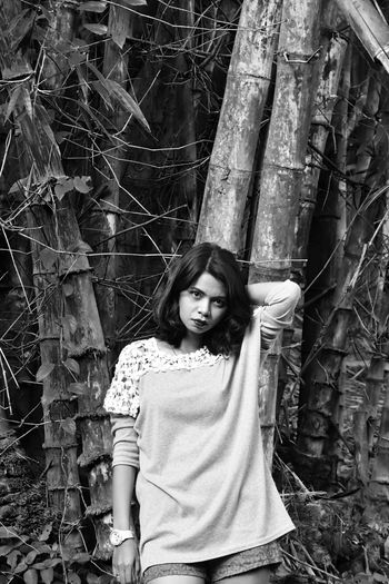 Portrait of woman standing against tree trunk in forest