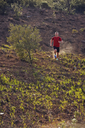 Rear view of man running in forest