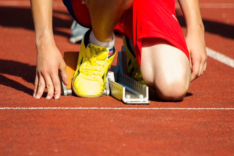 Sports event detail shot. 300mm Bundesjugendspiele Cropped Detail Footwear Human Body Part Human Hand Human Leg Knee Kneeling Low Section Men's 100 Meters On Your Mark Race School Sports Shoe Sneaker Sports Event  Sports Photography Sprint Starting Line Tension Winner