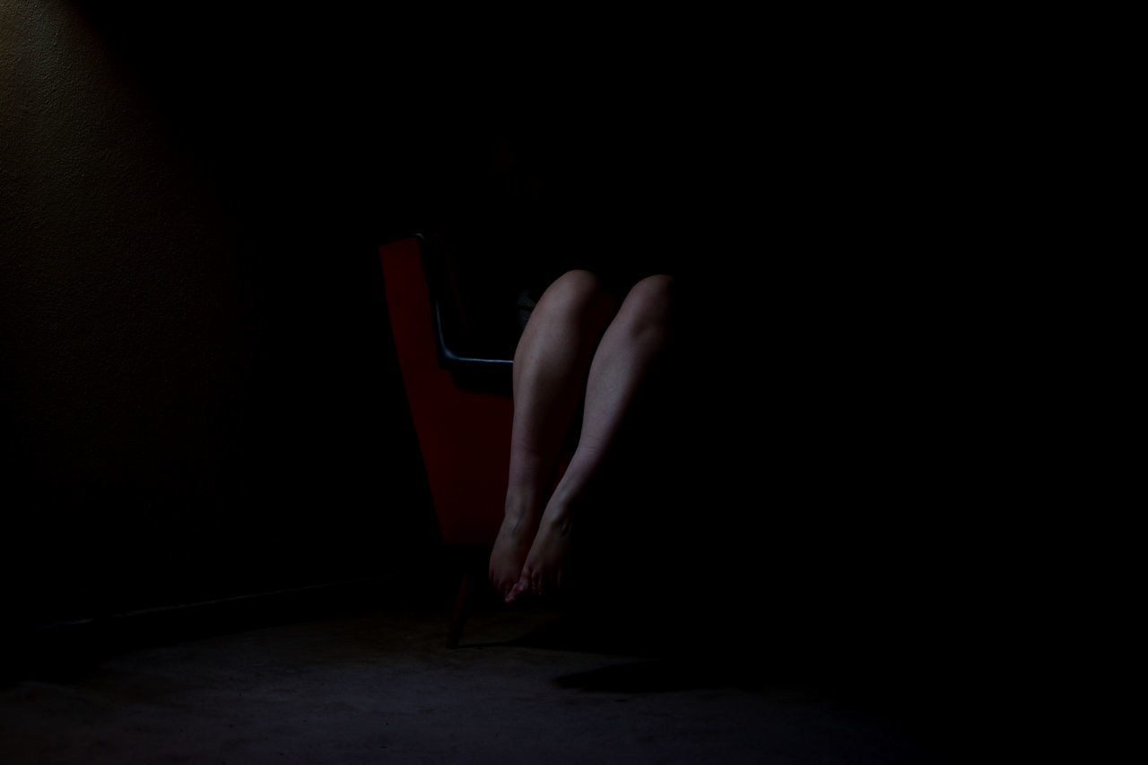 LOW SECTION OF WOMAN STANDING ON BLACK BACKGROUND