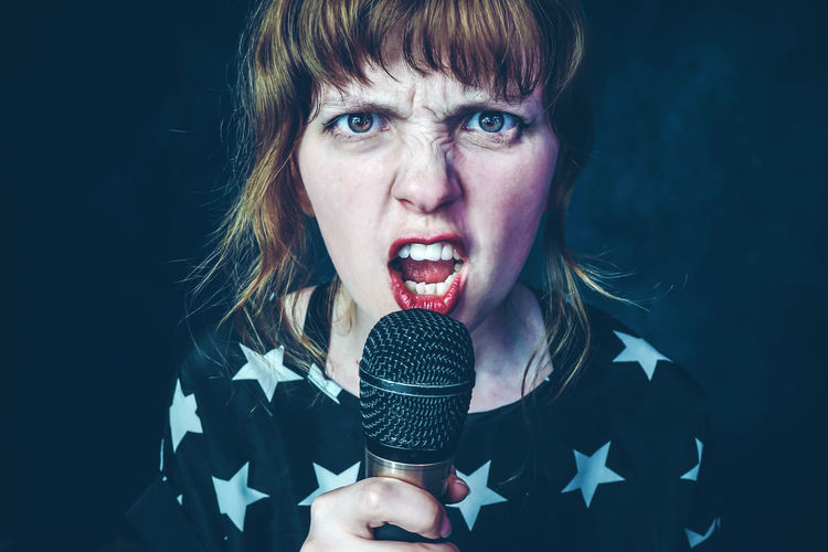 Microphone Input Device One Person Portrait Young Adult Adult Indoors  Women Singing Studio Shot Looking At Camera Headshot Front View Music Young Women Performance Holding Arts Culture And Entertainment Mouth Open Hairstyle Blue Background Scream Media Angry